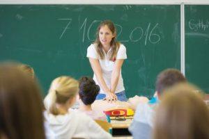 Lehrerin vor ihrer Klasse. Kindern mit ADS ebenso wie Kindern mit Hochbegabung sollte sie Struktur und Transparenz bieten.